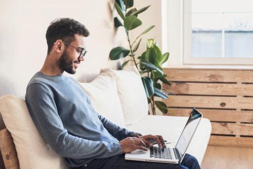 笑顔でパソコンをいじる男性の画像