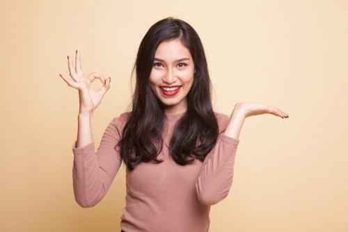 笑顔でOKサインをする女性の画像